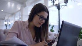 De online zaken, succesvol freelancerwijfje combineren het werk en studie gebruikend moderne computertechnologie met smartphone stock footage