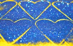 De onscherpe abstracte achtergrond met harten van blauw schittert fonkeling op gele oppervlakte Stock Fotografie