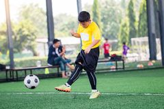 De onscherpe bal met de Aziatische snelheid van de jong geitjevoetballer loopt om bal aan doel op kunstmatig gras te schieten stock fotografie