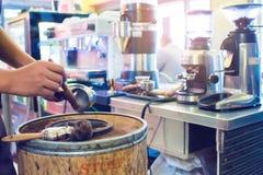 De onscherpe hand giet grondkoffie van machine in een houten emmer met onscherpe koffiemachine bij barteller in restaurant royalty-vrije stock afbeeldingen