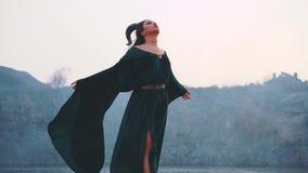 De onschuldige jonge aantrekkelijke dame in lange smaragdgroene velorkleding met vrije vliegende kokers geeft ziel aan duivel, me stock footage
