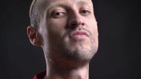 De ontevreden blonde mens hipster let op bij camera, zwarte achtergrond stock footage