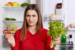 De ontevredenheid het vrouwelijke frown gezicht, aan dieet moet houden, eet slechts vruchten en groenten, houdt sla en de sandwic royalty-vrije stock foto's
