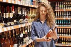 De ontevredenheid de krullende jonge vrouw in denimkleren met ongelukkige uitdrukking fles wijn bekijkt, leest de informatie aan  stock afbeeldingen