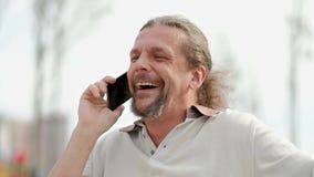 De ontspannen aantrekkelijke midden oude mens met lang grijs haar spreekt op smartphone, lacht en glimlacht stock video