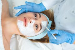 De ontspannen jonge vrouw krijgt de gezichtsbehandeling van de huidzorg bij schoonheidssalon De schoonheidsspecialist raakt borst stock foto
