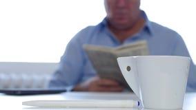 De ontspannen Koffie van Zakenmanuse cellphone drink en Gelezen Kranteninformatie stock videobeelden
