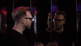 De ontspannen mens met glas van alcohol heeft een pret bij de disco Mens die in glazen de spiegel de bekijken, dan draait hoofd a stock videobeelden