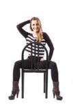 De ontspannen vrouwenzitting op een stoel glimlacht stock afbeelding