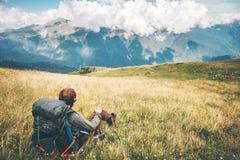 De ontspannende zitting van de mensenreiziger op grasvallei bij bergen Stock Afbeelding