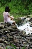 De ontspanning van de vrouw bij waterkant Royalty-vrije Stock Foto