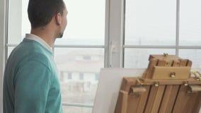 De ontstemde kunstenaar verloor inspiratie en gaat vanaf schildersezel stock videobeelden