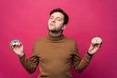 De ontstemde mens houdt twee de smakelijke ring donuts, ongelukkig voelt zoals afschuinen snoepjes, over roze achtergrond eet ver stock fotografie