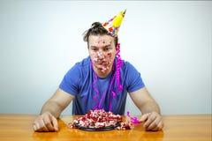 De ontstemde ongelukkige Kaukasische mens met kegelhoed op hoofd en verfrommelt cake neer kijkend met bored ontevreden uitdrukkin royalty-vrije stock afbeeldingen