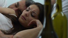 De ontwaken van de katervrouw in bed met vreemdere lege wijnflessen op lijst, schande stock videobeelden