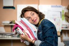 De ontwerper die van de vrouwenmanier zacht een stapel van kleren koesteren dient binnen de workshop in royalty-vrije stock foto's