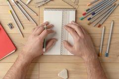 De ontwerper trekt een schets in een notitieboekje op een houten lijst kantoorbehoeften Mening van hierboven royalty-vrije stock afbeeldingen