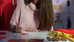 De ontwerper trekt een schets van een rode kleding, op een ledenpop hangt een steekproef van deze kleding Sluit omhoog stock footage
