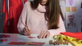 De ontwerper trekt schetsen, op manicene hangt een patroon van rode kleding Sluit omhoog stock footage