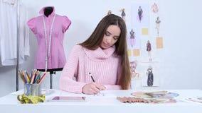 De ontwerper trekt schetsen voor een maniertijdschrift van vrouwen` s kleding stock footage
