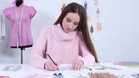 De ontwerper trekt schetsen voor een maniertijdschrift van vrouwen` s kleding stock video