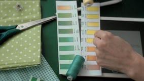 De ontwerperkleren van de lijstnaaister, zijaanzicht, groene achtergrond stock footage