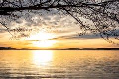De ontworpen mooie oranje zonsondergang van het de winterlandschap over kalm meerwater met heldere zon tegen overzeese horizon royalty-vrije stock fotografie