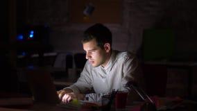 De ontzagwekkende Kaukasische zakenman werkt bij zijn Desktop, gebruikend computer terwijl het laat - nacht in bureau donker is,  stock video