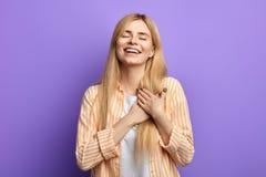 De ontzagwekkende lachende jonge vrouw met gesloten ogen houdt beide palmen op borst royalty-vrije stock foto's