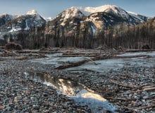 De onverzadigde Donkere Berg Relection van de Rivieroever Stock Foto's