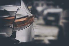 De onverzekerde die auto, met plakband wordt hersteld, de koplamp en zijn delen plakken uit stock fotografie
