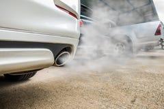 De onvolledige verbranding leidt tot giftige koolmonoxide van uitlaatpijp van witte auto, luchtvervuilingsconcept stock foto's