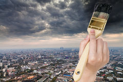 De onweerswolken van penseelverven over donkere stad Stock Foto's