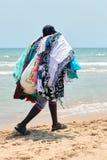 De onwettige verkoper van stoffen, kleding, glazen, loopt op het strand Stock Foto's