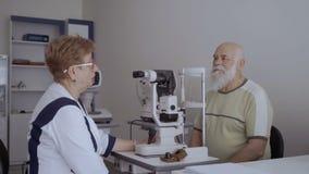De oogarts geeft overleg aan de oude mens stock video