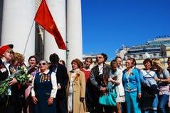 De oorlogsveteranen zingen oorlogsliederen De sovjetgolven van de leger rode vlag boven mensen Royalty-vrije Stock Foto's