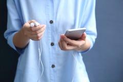 De oortelefoon van de vrouwenholding met het gebruiken van smartphone voor luistert lied Stock Fotografie