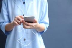 De oortelefoon van de vrouwenslijtage met het gebruiken van smartphone voor luistert lied Royalty-vrije Stock Foto