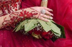 De oostelijke bruid dient een rode kleding met een trouwring en een boeket van rozen in Stock Foto