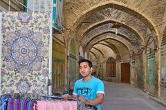 De oosterse tapijtenverkoper stelt goederen voor verkoop in oostelijke bazaar bloot stock foto