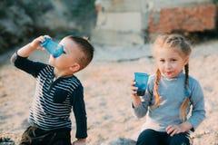 De de op zee kinderen, broer en de zuster drinken van plastic blauwe koppen van water of sap stock afbeelding