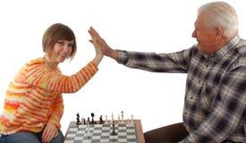 De opa en de kleindochter maken een compromis in schaak stock afbeelding