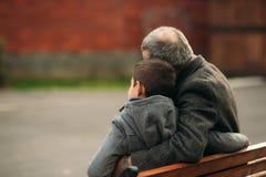 De opa en zijn kleinzoon brengen samen tijd in het park door Zij zitten op de bank Achter mening royalty-vrije stock foto