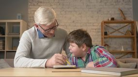 De opa helpt een kleinzoon met thuiswerk Het bejaarde helpt een jong vet kind om thuiswerk te doen Huiscomfort, familieidylle stock videobeelden