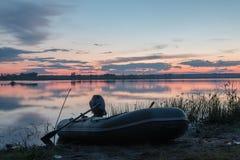 De opblaasbare die boot met de motor dichtbij de kust van de vijver bij zonsondergang wordt vastgelegd Royalty-vrije Stock Afbeelding