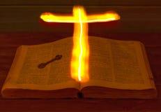 De open Heilige Bijbel is op de lijst Oude Sleutel Het Heilige Kruis gloeit over de Bijbel en verlicht zijn pagina's Brandend Kru royalty-vrije stock afbeeldingen