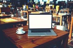 De open laptop computer en de kop van koffie die op een houten lijst in koffie liggen versperren binnenland royalty-vrije stock foto