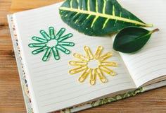 De open pagina van het notaboek, gekleurde klemmen en groen blad Houten achtergrond Selectieve nadruk stock foto