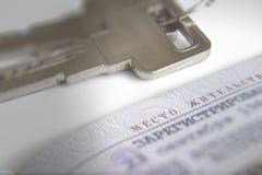De open pagina van het paspoort van de burger en de sleutels op een wit stock foto's