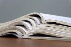 De open tijdschriften liggen bovenop elkaar op een bruine lijst, zijn de documenten gestapeld close-up stock foto